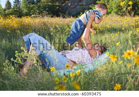 Mother and son cuddling and playing in late afternoon sun - stock photo