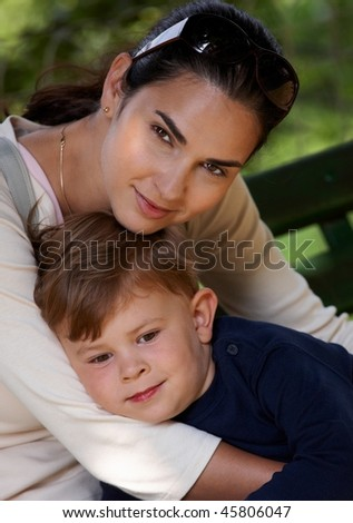 Mother and son cuddling together outdoor, smiling. - stock photo