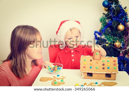 mother and son decorating gingerbread house, christmas theme