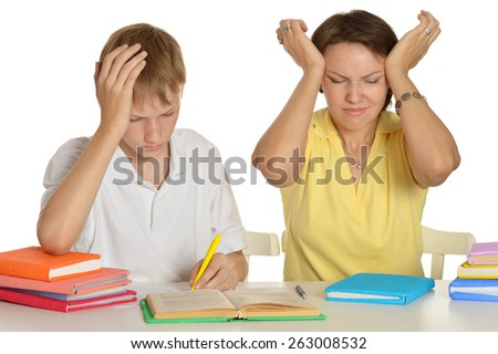 Mother and son doing homework together on a white background - stock photo