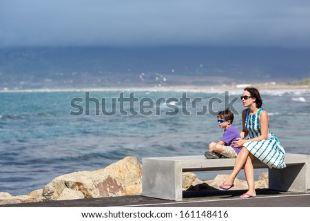Mother and son enjoying beautiful ocean view - stock photo