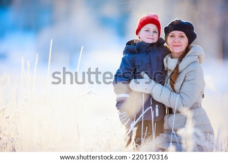 Mother and son enjoying beautiful winter day with snow outdoors