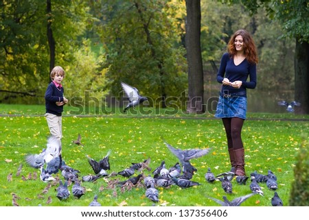 Mother and son feeding pigeons in a park - stock photo