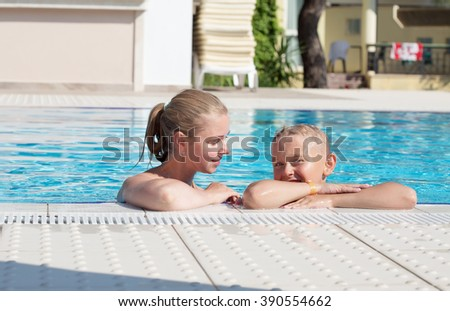 Mother and son have fun by a swimming pool - stock photo