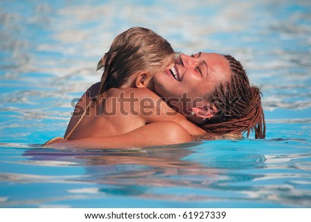 Mother and son have fun swimming in the pool with turquoise water - stock photo