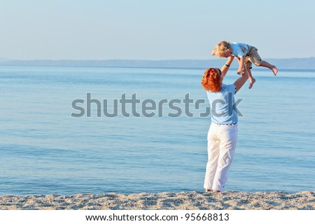 Mother and son having fun at the beach in summer