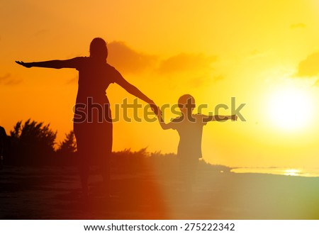 mother and son having fun on sunset beach - stock photo