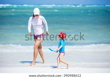Mother and son having fun on the beach - stock photo