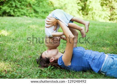 Mother and son having fun on the grass in a park - stock photo