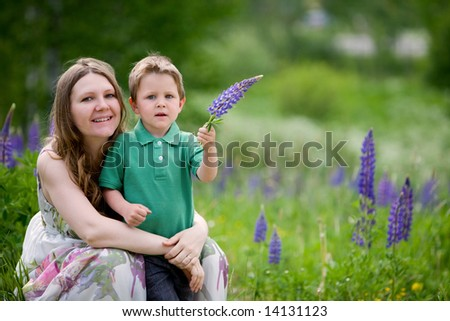 Mother and son having fun outdoors at sunny summer day - stock photo