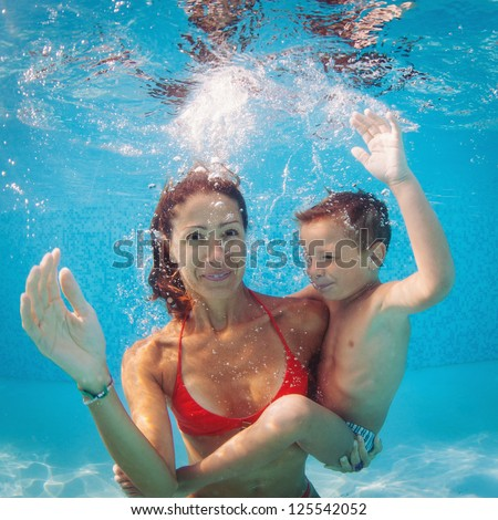 Mother and son having fun underwater in swimming pool.