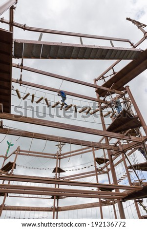 Mother and son high up on an obstacle course - stock photo