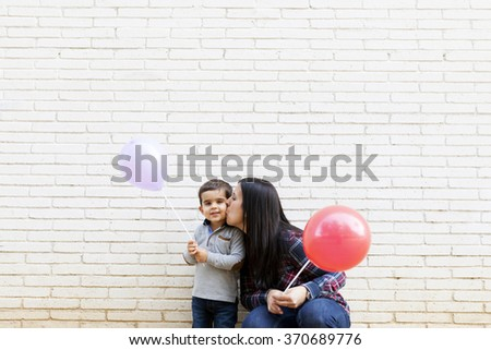mother and son holding balloons on a white wall - stock photo