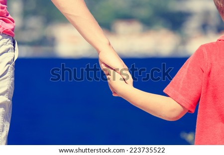 mother and son holding hands on sea vacation - stock photo