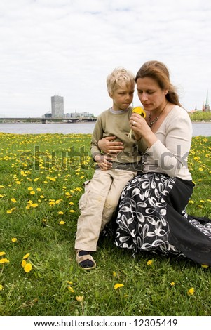 Mother and son in Dandelion meadow. Riga city in background - stock photo