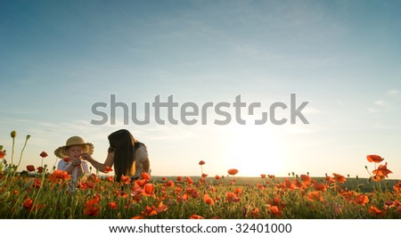 mother and son in poppy field - stock photo