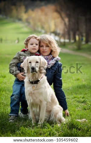 Mother and son in the park along with a golden retriever. - stock photo