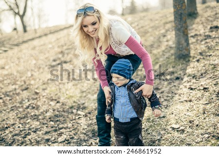mother and son in the park on a sunny day in early spring. Bokeh. Vignetting. shallow depth of field. Toned image - stock photo