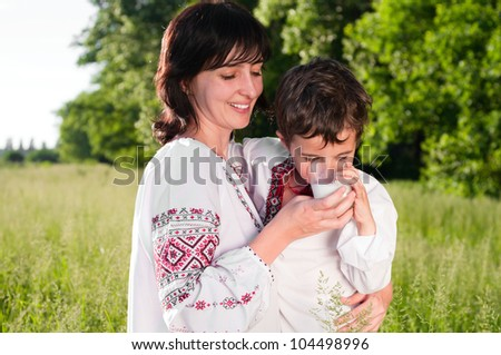 Mother and son in traditional ukrainian shirt drink milk outdoors on the summer meadow - stock photo