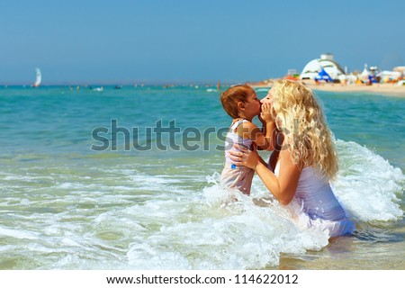 mother and son kiss in sea water on beach - stock photo