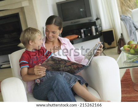 Mother and son (5-7) looking at photo album at home, boy in mother's lap in armchair, smiling (tilt)