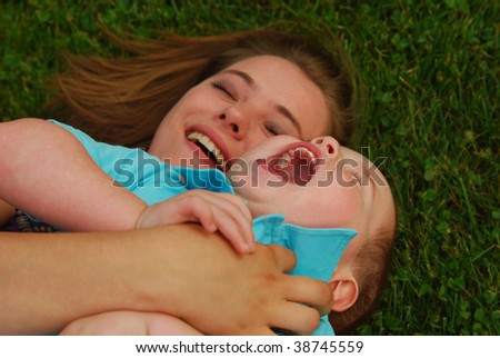 Mother and son lying on grass laughing. Shallow depth of field, focus on boy's mouth. - stock photo