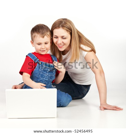 Mother and son lying on the floor with laptop on white background - stock photo