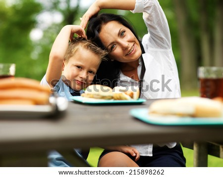 mother and son making heart shape at picnic - stock photo