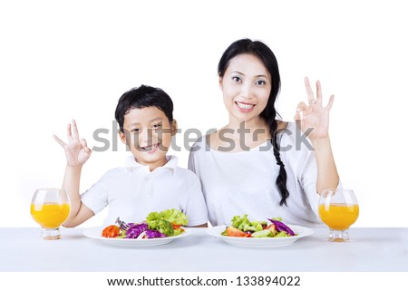 Mother and son making OK gesture while having salad, isolated on white - stock photo