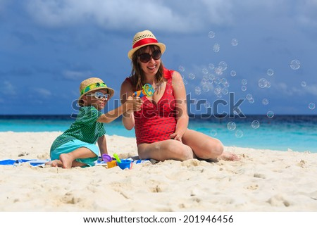 mother and son making soap bubbles on tropical beach - stock photo