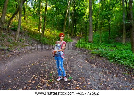 Mother and son on vacation in green forest. Beautiful nature landscape. Family traveling, spending time together. Mom hug kid, little baby boy, having fun outdoors on wild nature forest trees. - stock photo