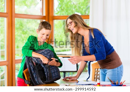Mother and son packing school bag for next day - stock photo
