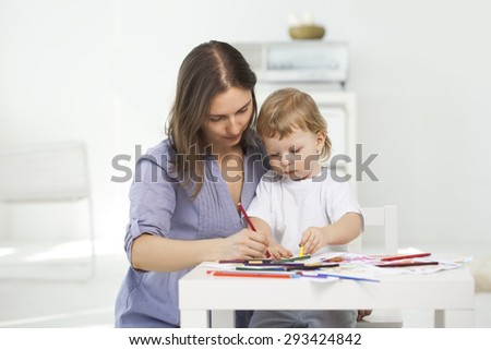mother and son paint indoors - stock photo
