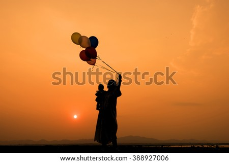 mother and son play balloon silhouette at sunset