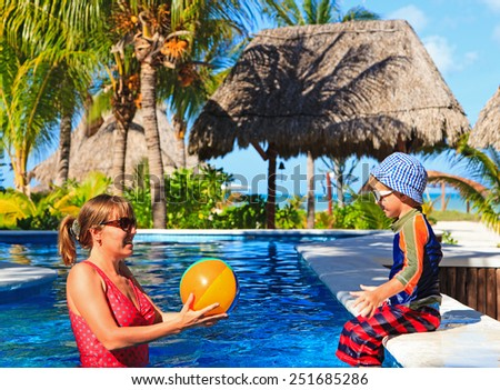 mother and son playing ball at the pool on tropical beach - stock photo