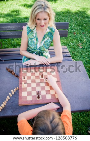 Mother and Son playing Chess - stock photo