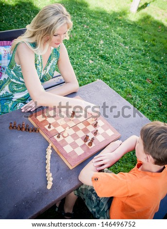 Mother and son playing chess outdoor - stock photo