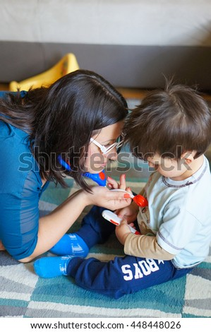 Mother and son playing doctor with medical toys - stock photo