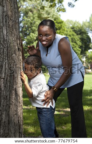 Mother and son playing hide and seek at a park - stock photo