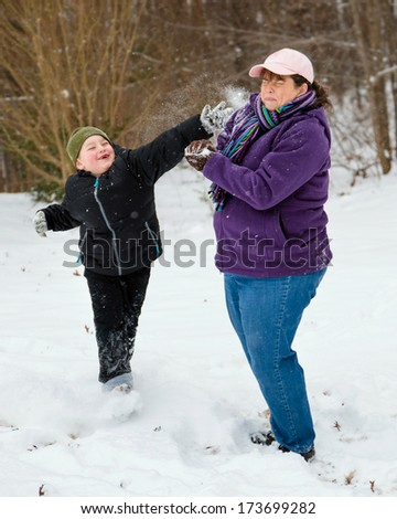 Mother and son playing in snow by having snowball fight - stock photo
