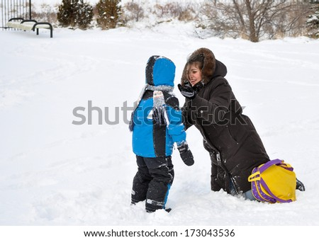 Mother and son playing in the snow. Single mother picking her son up at school during winter - stock photo