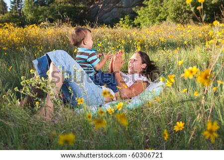 Mother and son playing on a blanket in nature - stock photo