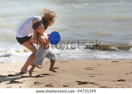 mother and son playing on beach - stock photo