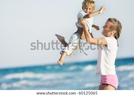 mother and son playing on sea background - stock photo