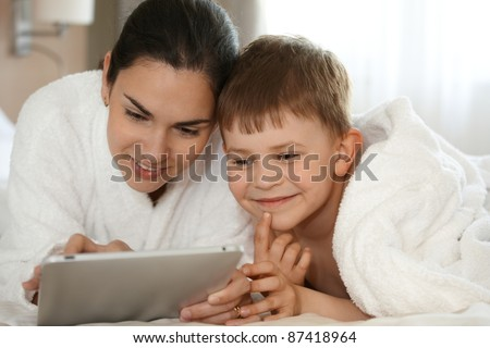 Mother and son playing on tablet, smiling, laying on bed. - stock photo