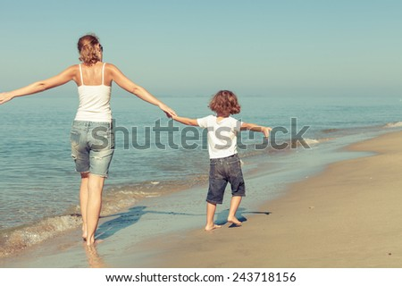 Mother and son playing on the beach at the day time. Concept of friendly family. - stock photo