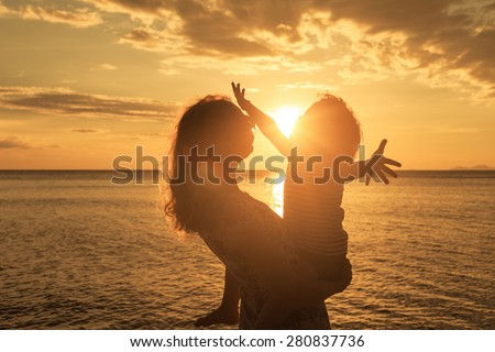 Mother and son playing on the beach at the sunset time. Concept of friendly family.