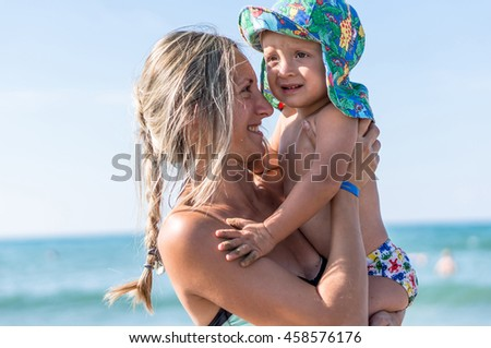 Mother and son playing on the beach in the day time. Happy family. Positive human emotions, feelings, joy.