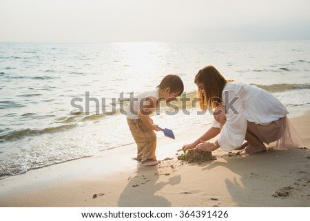 mother and son playing on the beach,vintage filter - stock photo