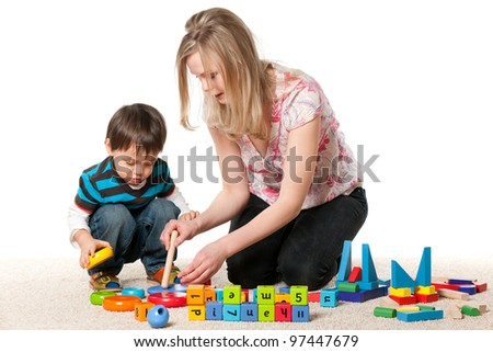 Mother and son playing on the carpet with blocks; isolated on the white background - stock photo
